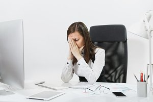Tired perplexed and stress brown-hair business woman in suit sitting at the desk, covering her face with hands, working at contemporary computer with documents in light office on white background