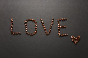 Top view of letter love, word made from coffee beans on black background for design. Saint Valentine's Day card on fabruary 14, holiday concept. Copy space for advertisement.