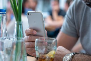 man in bar holding smartphone