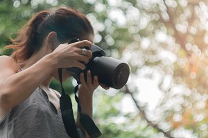 Woman is a professional photographer with dslr camera, soft focus, natural bokeh