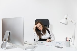 Beautiful tired stress brown-hair business woman with headache sitting at the desk, working at contemporary computer with modern monitor with documents in light office, on white background