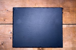 Black stone board on wooden table