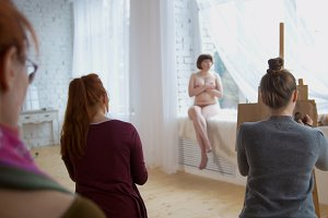Young women artists performing artistic etude with naked model in drawing studio
