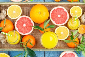 Different fruits and glass with fresh orange juice