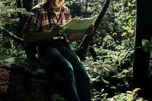 hipster exploring map in forest