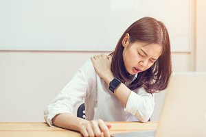 Asian girl in white casual dress catch that shoulder, Because of the pain of hard work. Or something hit the shoulder. on the room office.