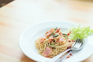 Spaghetti pasta with ham and a spoon on the table. Natural light tableware.