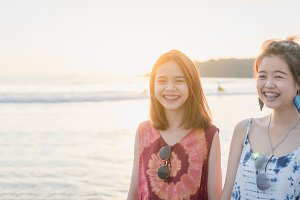 Summer time, portrait of two young women walking on the beach and smiling. In the evening, the sun from behind beautiful.