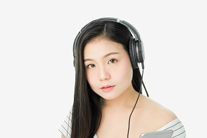 Asian Women are listening to music from black headphones. In a comfortable and good mood, on a white background gives a soft light.