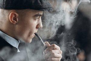 stylish man smoking wooden pipe