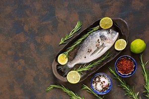 Raw dorado fish with lime and spices in a ceramic dish on a brown background. Top view, copy space.
