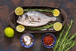 Raw dorado fish with ingredients for cooking. View from above. The concept of a healthy diet.