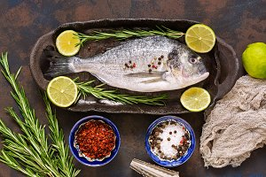 Fresh fish with spices on a dark background, top view. Raw dorado fish on a ceramic dish with lime and rosemary.