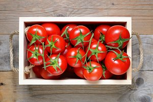 Ripe tomatoes in wooden box close-up