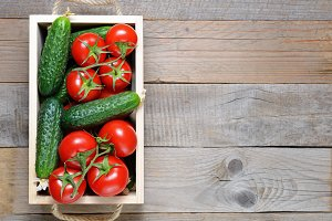 Tomatoes and cucumbers in wooden box