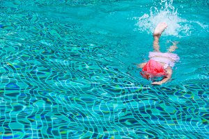 kid swimming on a blue water pool