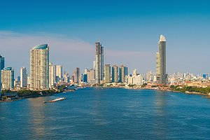 Financial district and Chao Phraya River with blue sky in Bangkok city, Thailand