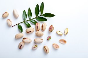 Pistachios with leaves on white