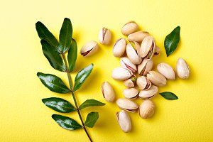 Pistachios with leaves on yellow