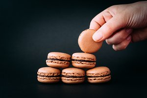 Woman placing macarons on heap on bl