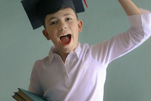 school teenager kid in graduation cap with books pile make happy gesture