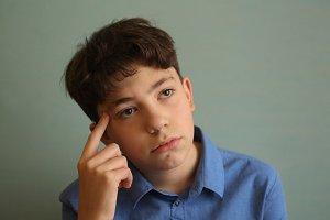 teenager boy close up thinking photo isolated on blue background