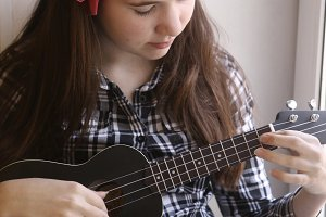 happy teen girl with ukulele guitar in checked shirt and jeans playing