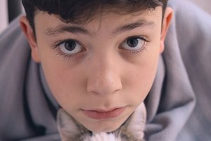 teenager kid boy and cat friends close up funny portrait