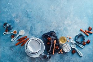Porcelain baking forms and muffin tin with whisks, spoons and spices on a marble kitchen table. Baking tools and ingredients with copy space. making pastry concept.