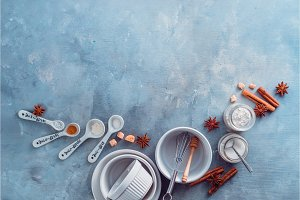 Porcelain baking forms with spoons, flour, sugar and spices on a marble kitchen table. Baking tools and ingredients with copy space. Making pastry concept.