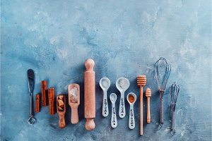 Measuring spoons, wooden scoops, whisks, rolling pin, honey spoons, sugar and cinnamon on a blue concrete background. Baking tools and ingredients concept flat lay with copy space.