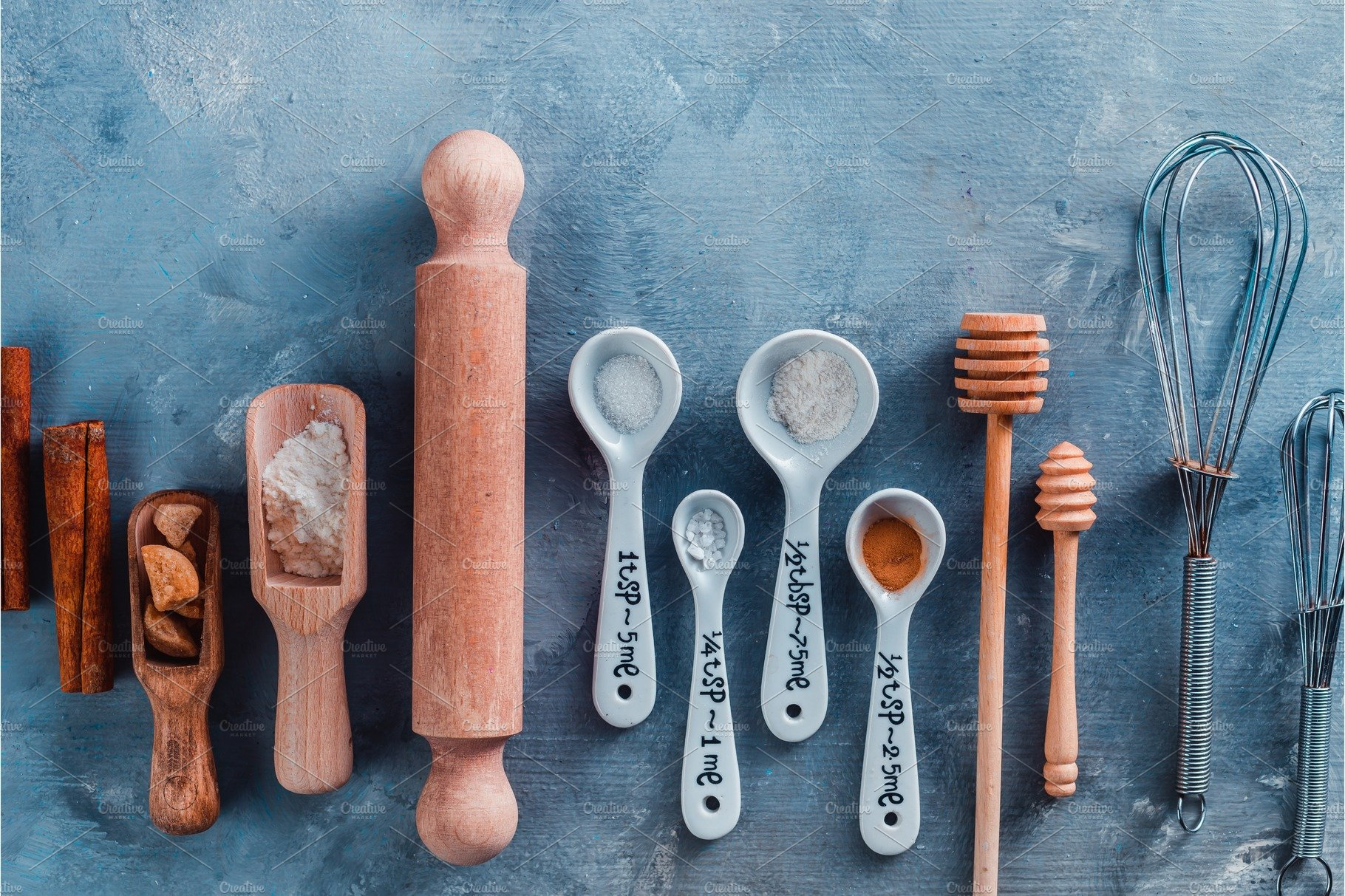 Kitchen utensils for baking, rolling pin and measuring spoons on a ...