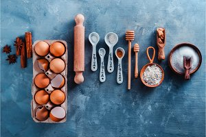 Baking pattern with measuring spoons, wooden scoops, whisks, rolling pin, sugar, flour, eggs and cinnamon on a blue concrete background. Baking tools and ingredients concept flat lay with copy space.