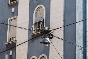 Electric wires and street lamp against building