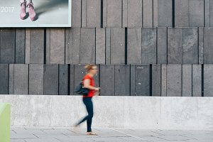 Woman moving against modern architecture concrete wall