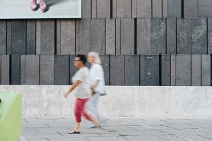 Women walking against modern architecture concrete wall
