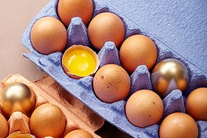 Dozen of chicken eggs in colorful cardboard container with one golden egg