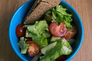 tomato cucumber olives salad with crispy rye bread close up