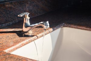 Close up of faucet and water flow