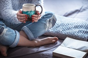 Girl holding a beautiful Cup and reading a book, against the background of home comfort.