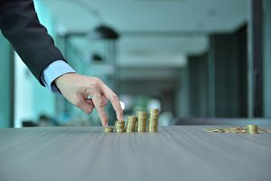 Businessman Stacking Coins in Increasing Order at desk
