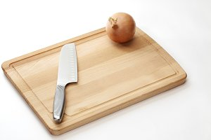 Knife and onion are placed on wooden chopping board