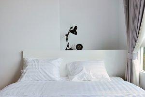 modern lamp on wooden nightstand in white modern bedroom, interior design