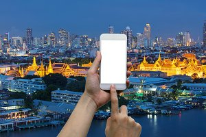 Hands touching smartphone in front of temple of emerald buddha, grand palace at night in Bangkok, Thailand