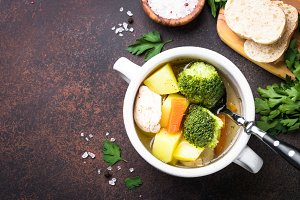 Chicken and vegetables soup on dark table.