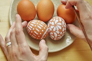 Female hands painting eggs with various white patterns for easter