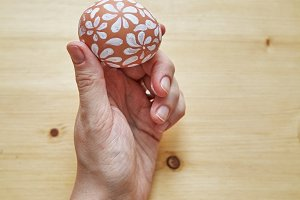 Female hands holding egg painted with white floral pattern for Easter holiday
