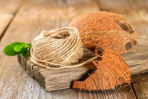 Rope of fiber coir and coconut shell on an old wooden table.