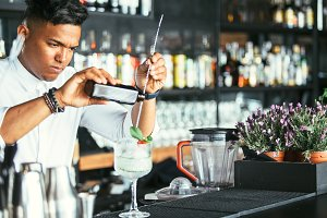 Expert bartender pouring alcohol