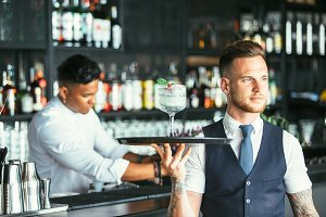 Elegant waiter serving a cocktail